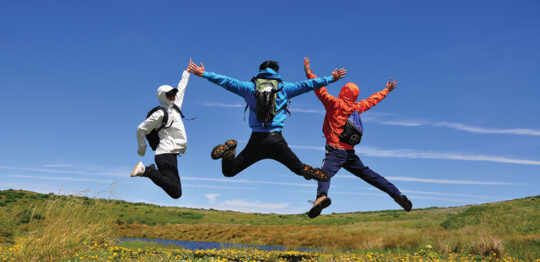 Three people jumping with their legs and arms extended