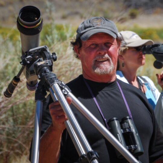 Rich Stallcup holding a spotting scope on a tripod