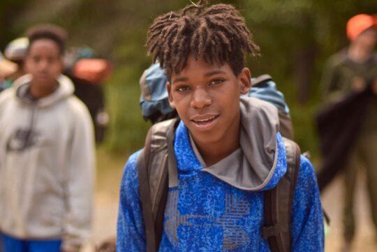 A boy wearing a backpacking backpack