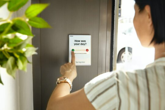 Female employee pressing a green button to give feedback on a device at the office exit door